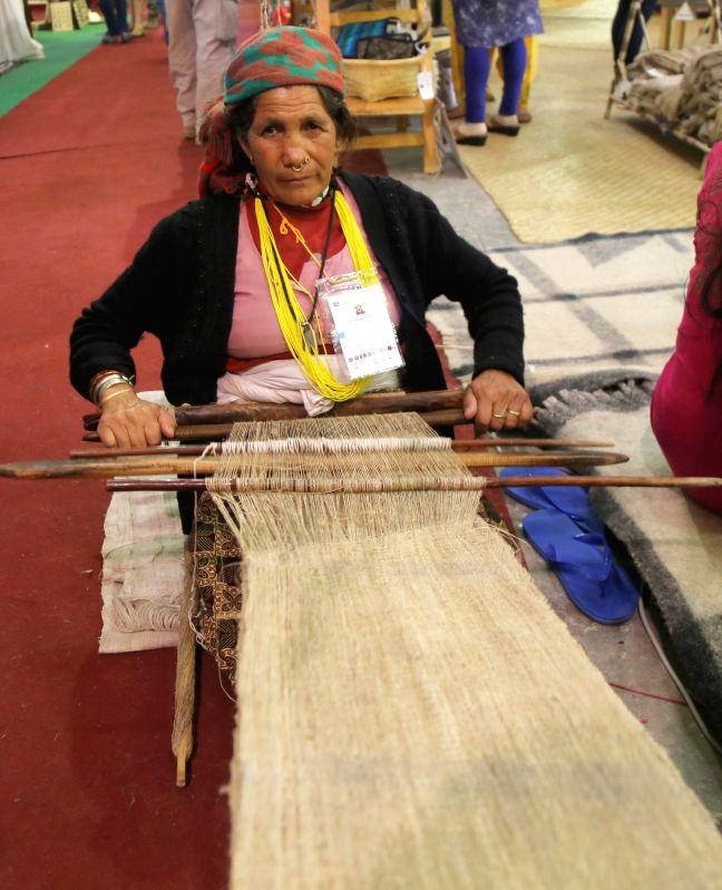 KATHMANDU, May 8, 2016 - A woman weaves cloth in a traditional style during the 13th Handicraft Trade Fair in Kathmandu, Nepal, May 8, 2016. The fair was organized by the Federation of Handicraft ...