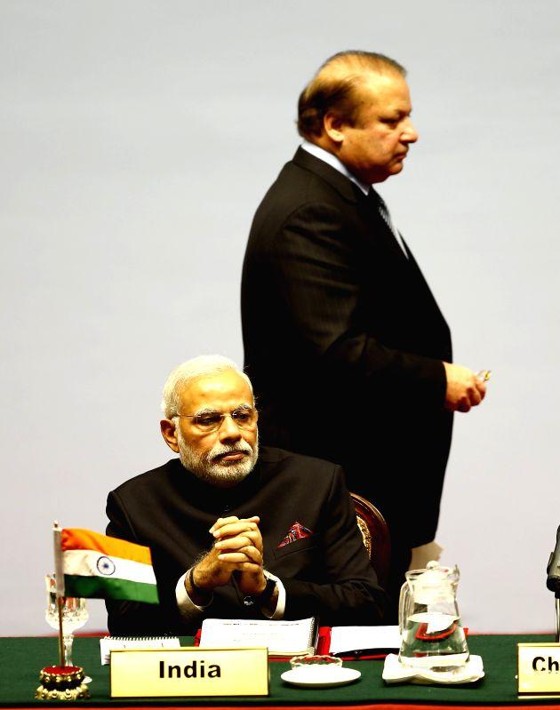 Kathmandu (Nepal): Pakistani Prime Minister Nawaz Sharif walks past Indian Prime Minister Narendra Modi during the opening session of the 18th South Asian Association for Regional Cooperation - Nawaz Sharif and Narendra Modi