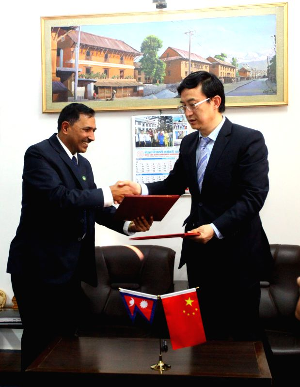 Kathmandu (Nepal): Purna Chandra Bhattarai (L), joint secretary at Ministry of Federal Affairs and Local Development of Nepal, shakes hands with Chinese Ambassador to Nepal Wu Chuntai during the ...