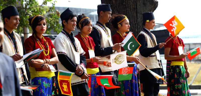 Nepalese youth in traditional attire wave flags at Tribhuwan International Airport in Kathmandu, Nepal, Nov. 25, 2014. After two years' postponement, the SAARC will see its 18th summit in .