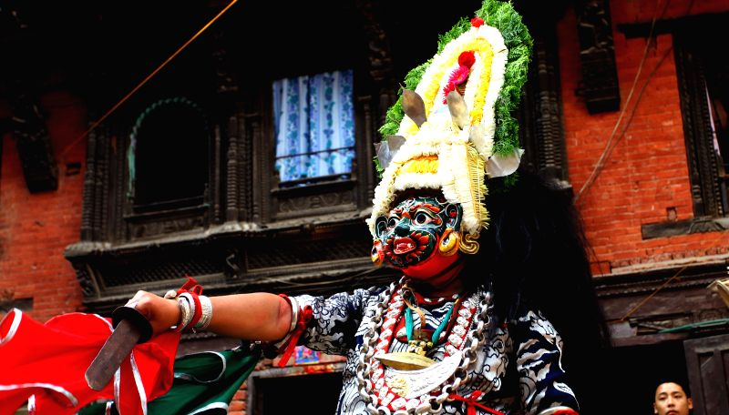 """A masked dancer performs as part of """"Devi Pyankha"""" (Devi Dance) to mark the beginning of Indrajatra Festival in Kathmandu, Nepal, Sept. 3, 2014. ..."""