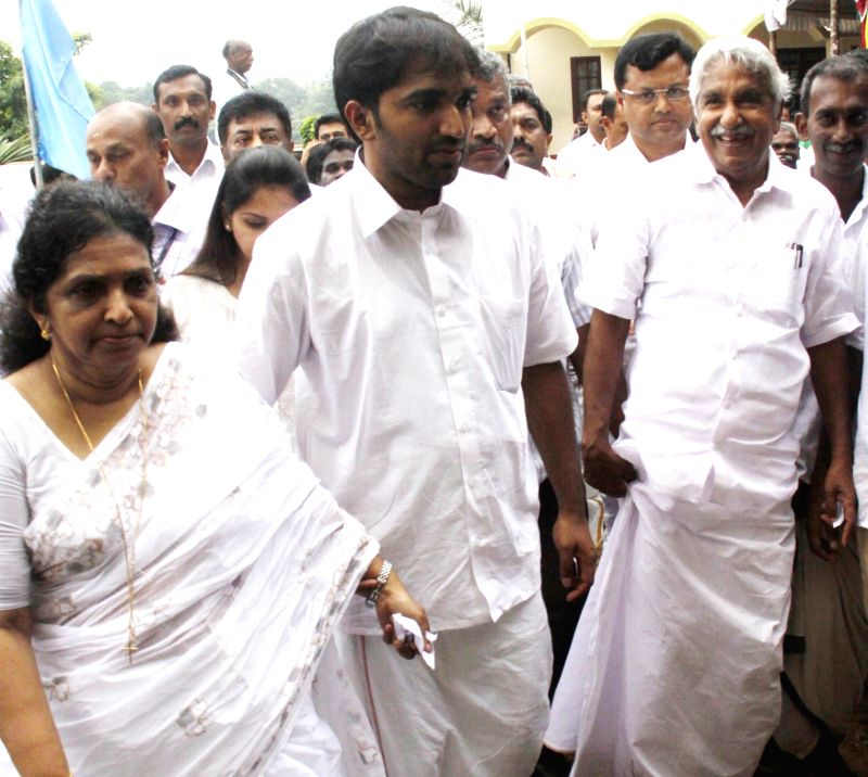 Kerala chief minister Oommen Chandy and his family arrive to cast their votes at a polling booth in Puthuppally of Kerala's Kottayam sistrict during state assembly polls  on May 16, 2016. - Oommen Chandy