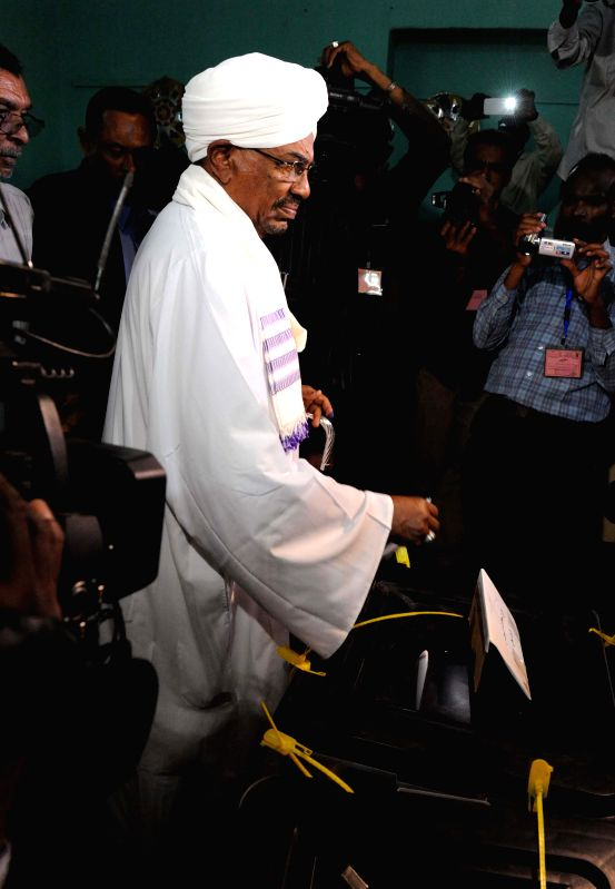 Sudan's President Omar al-Bashir arrives at a polling station to cast his ballot in Khartoum, Sudan, April 13, 2015. Voters in Sudan started casting their votes ...