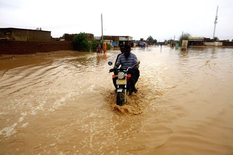 KHARTOUM, Aug. 3, 2018 - Local citizens wade through rainwater in Khartoum, Sudan, Aug. 3, 2018.