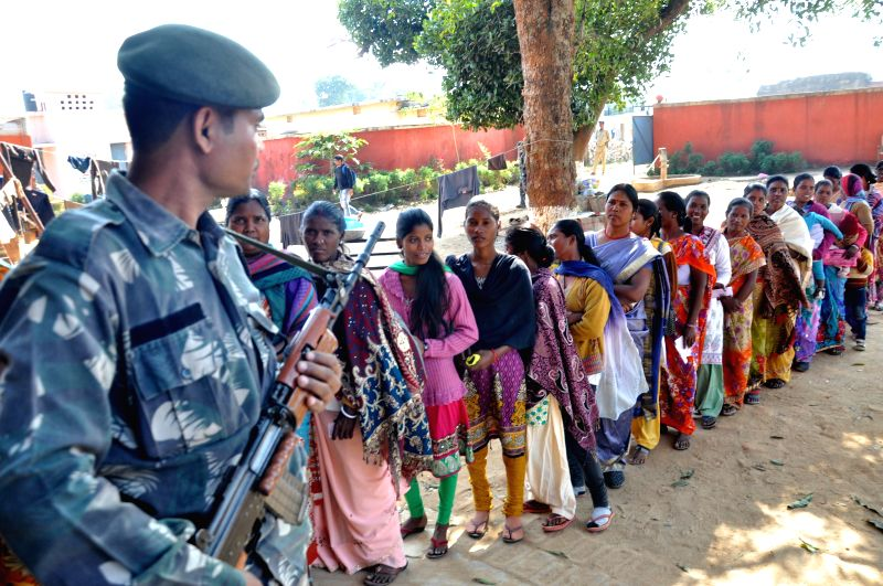 A soldier stands guard at a polling booth as women queue-up to cast their votes during the third phase of Jharkhand assembly polls in Maoist infested Rampur village, near Khijri on Dec 9, ...