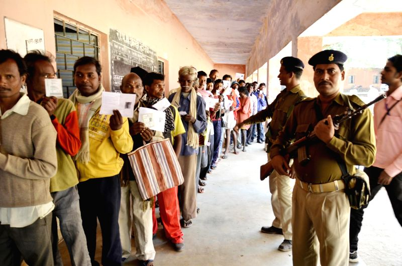 Soldier stand guard at a polling booth as people queue-up to cast their votes during the second phase of Jharkhand assembly polls in Maoist infested Khunti district on Dec 2, 2014.