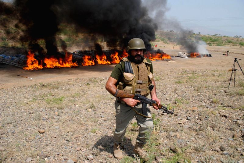 A Pakistani soldier stands guard as piles of drugs burn during a ceremony to mark the International Day Against Drug Abuse and Illicit Trafficking in Shakas ..
