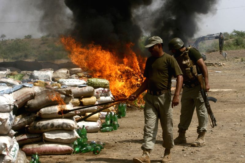 Pakistani security officials torch piles of drugs during a ceremony to mark the International Day Against Drug Abuse and Illicit Trafficking in Shakas area of