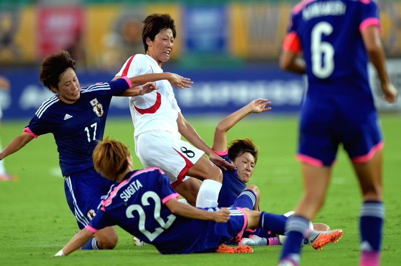 Kim Un Jun (C) of the Democratic People' s Republic of Korea (DPRK) is tackled by Japanese players during their match at the 2015 EAFF(East Asian Football Federation) ...