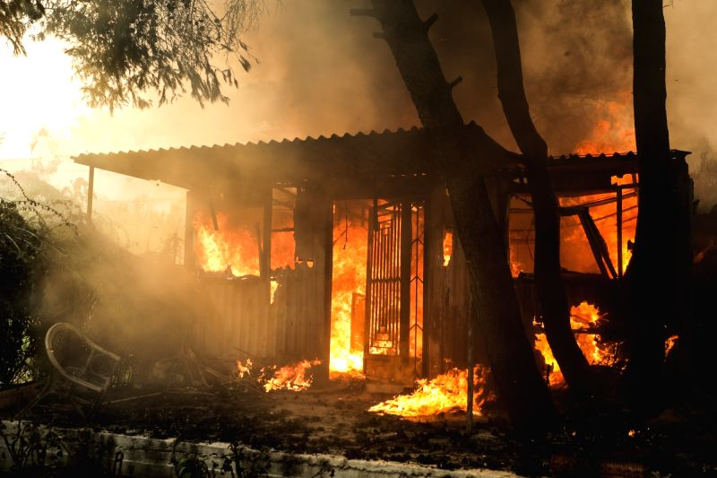 KINETA (GREECE), July 23, 2018 A house is seen burning amid wildfire in the town of Kineta near Athens, Greece, July 23, 2018. Western and Eastern Attica were declared in state of ...