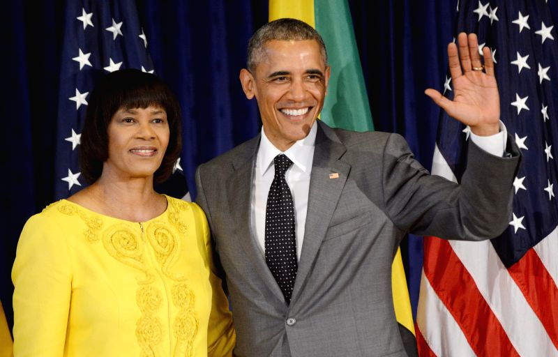 US President Barack Obama (R) next to the Primer Minister of Jamaica, Portia Simpson-Miller (L), poses for the press during the first official act of Obama's agenda in Kingston, Jamaica, 09 ...