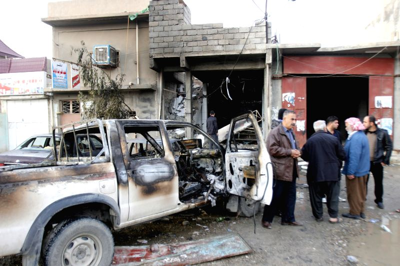 A damaged car is seen at an explosion site in the city of Kirkuk, Iraq, Dec 5, 2014. A suicide bomber with an explosive vest blew himself up in a cafe in the northern Iraqi city of Kirkuk, ...