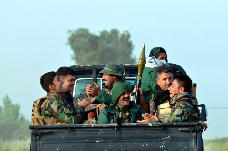 A group of Kurdish peshmerga forces and Hashid Shaabi forces are seen on a military vehicle on the way to the front line in the Bashir village, 20 km south of ...