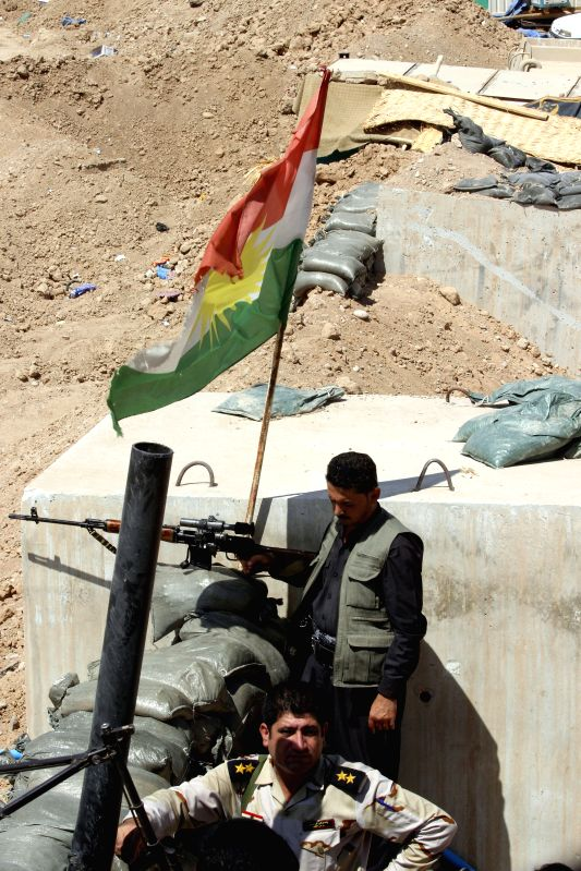 """Kurdish fighters guard on the """"border"""" of the Islamic State militants and Kurdish fighters on the road to Tikrit in Kirkuk, Iraq, Aug. 23, 2014. ..."""