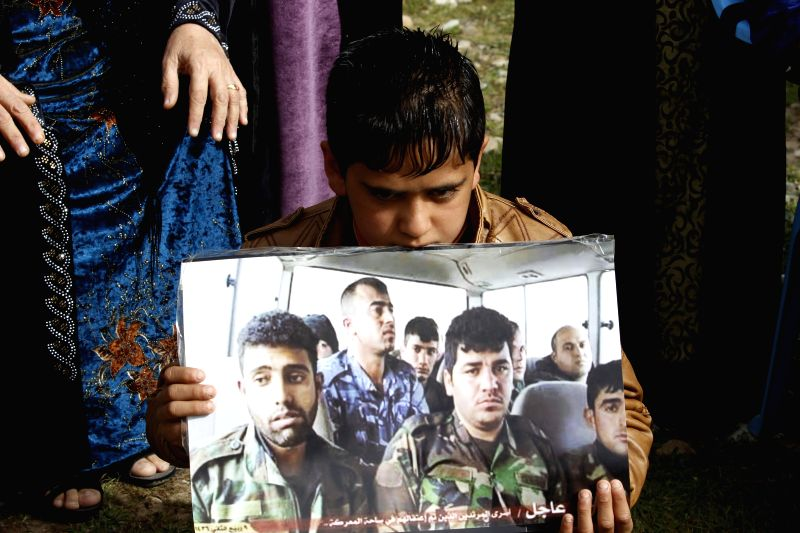 A Kurdish child holds a picture during a rally demanding release of captives captured earlier by IS militants at the Khalid's Office, 25 km west of Kirkuk, northern .