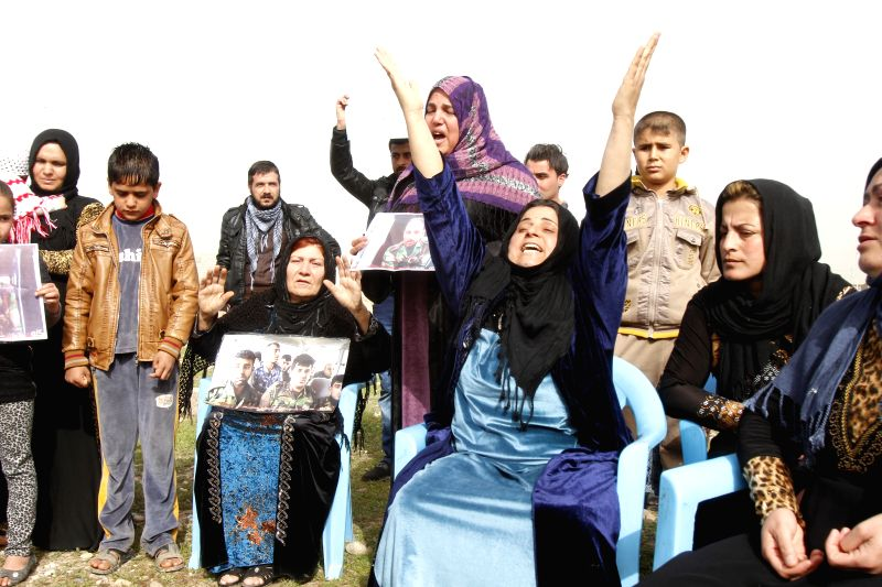A Kurdish woman raise her hands during a rally demanding release of captives captured earlier by IS militants at the Khalid's Office, 25 km west of Kirkuk, northern .