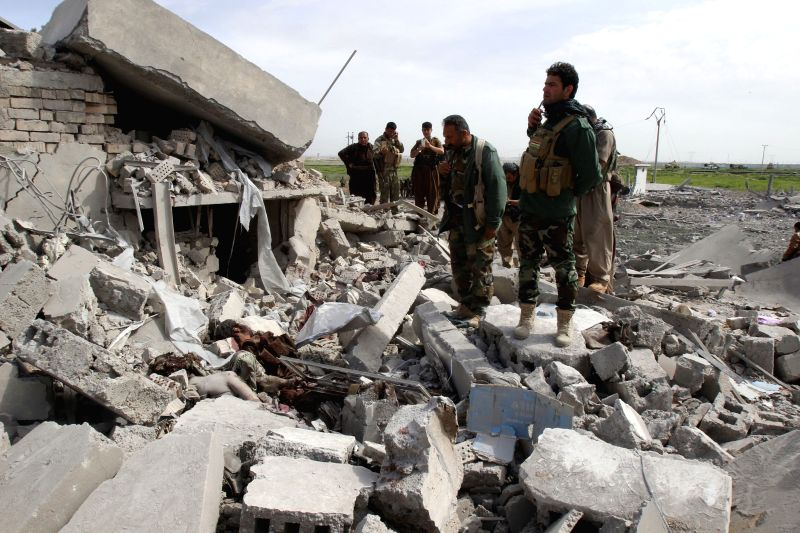 Kurdish peshmerga forces inspect a destroyed building on the outskirts of Tel Ward, west of the city of Kirkuk, Iraq, March 9, 2015. Kurdish security forces, known ...