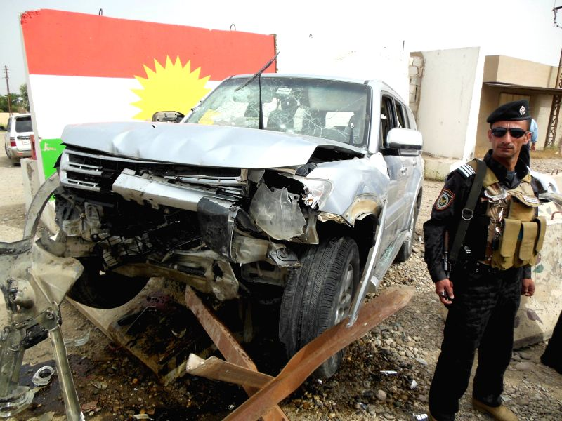 KIRKUK, May 2, 2017 - A security member stands guard near a car that hit a concrete barrier after being attacked by gunmen in southwestern Kirkuk, some 250 km north of the Iraqi capital of Baghdad, ...