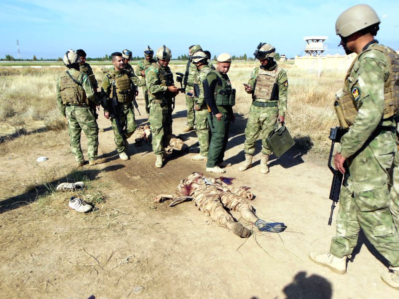 KIRKUK, May 7, 2017 - Kurdish force, also known as Peshmerga, stand around the bodies of the suicide bombers after killing them at a Kurdish military base near Iraq's northern city of Kirkuk, May 7, ...