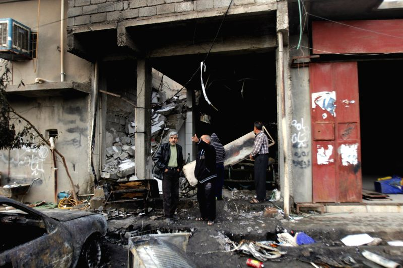 People watch a damaged building at an explosion site in the city of Kirkuk, Iraq, Dec 5, 2014. A suicide bomber with an explosive vest blew himself up in a cafe in the northern Iraqi city of .