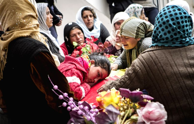 Kurdish people mourn beside the coffins of Kurdish fighters during a funeral ceremony in Kobane, Syria, on April 2, 2015. Five Kurdish fighters died in clashes with ...