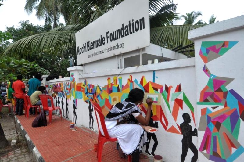 Volunteers and art students paint graffiti on the boundary walls of Kochi Biennale Foundation office in Kochi  on Dec 18, 2014.