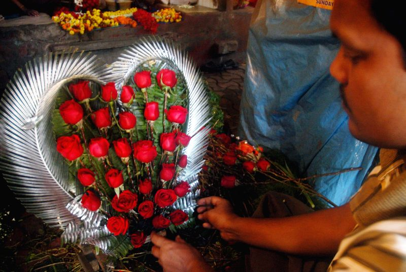A flower-monger makes a bouquet on Valentine's Day in Kolkata, on Feb 14, 2015.