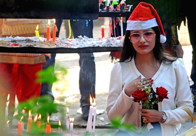 A girl prays at St Paul's Cathedral on Christmas in Kolkata, on Dec 25, 2014.