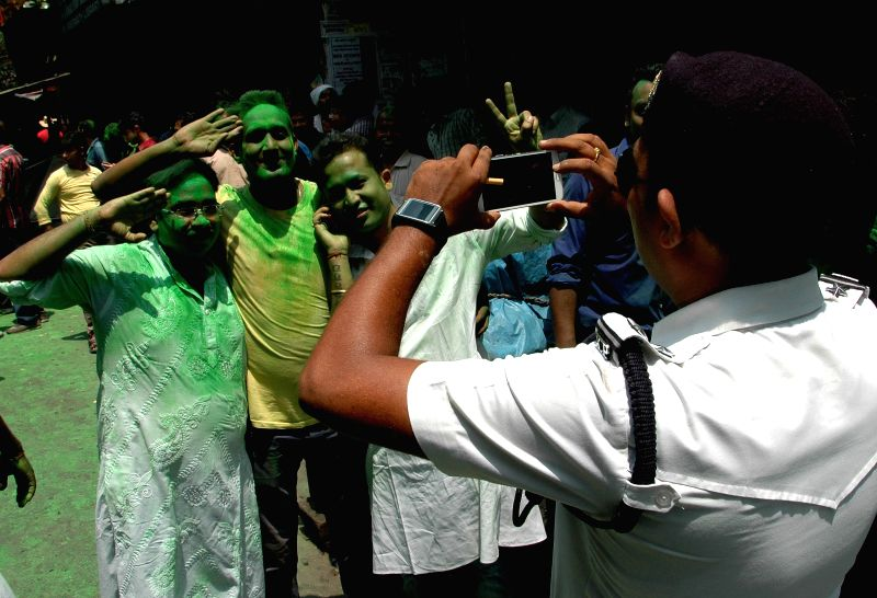 A policeman clicks pictures of Trinamool Congress workers celebrating party's performance in the recently concluded KMC polls in Kolkata, on April 28, 2015.