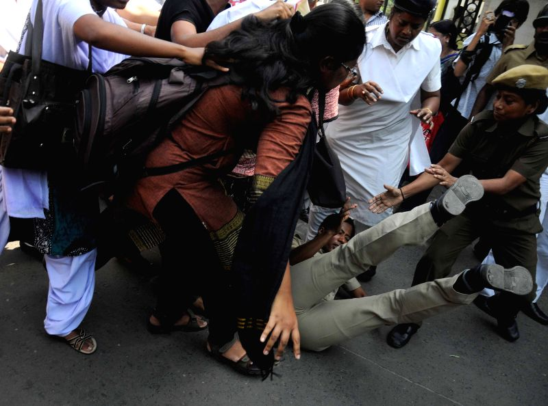 A policewoman falls on the ground while trying to control the  DSO activists demonstrating outside Raj Bhawan to press for re-introduction of pass-fail system in schools in Kolkata on April ...