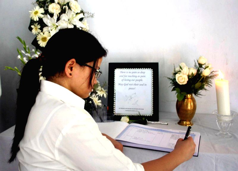 A woman writes condolence message for Nepal earthquake victims at the Nepal Consulate in Kolkata, on May 4, 2015.