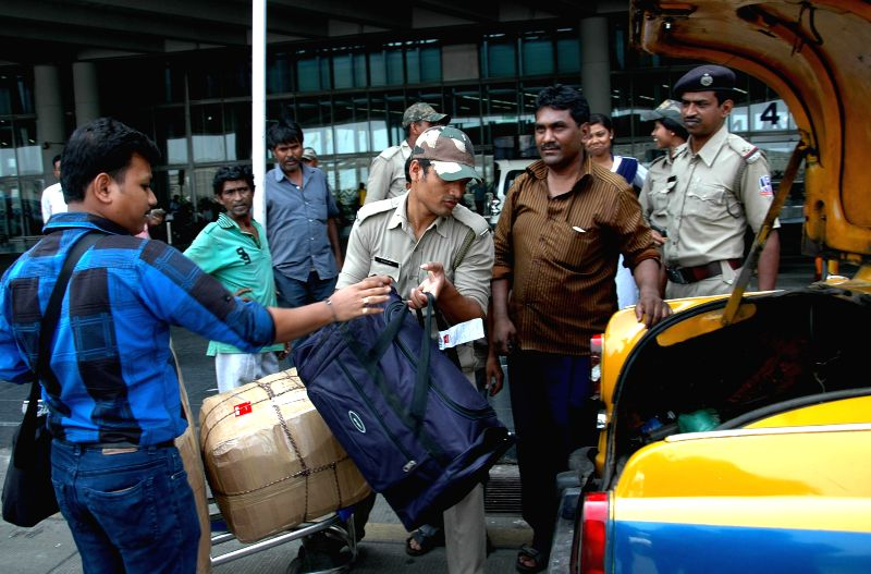 Army personnel help passengers outside the Netaji Subhas Chandra Bose International Airport during a 12 hour general strike called by opposition parties in Kolkata on April 30, 2015.