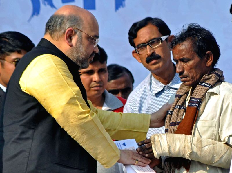 BJP chief Amit Shah hands over a cheque to a relative of a BJP worker killed in recent political clash in West Bengal's Birbhum district during a party rally in Kolkata, on Nov 30, 2014.