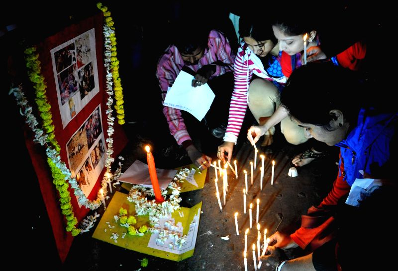 BJP supporters participate in a candle light vigil to protest against Tuesday's attack on the Army Public School in Peshawar, Pakistan, that claimed 104 lives mostly those of children, in ...