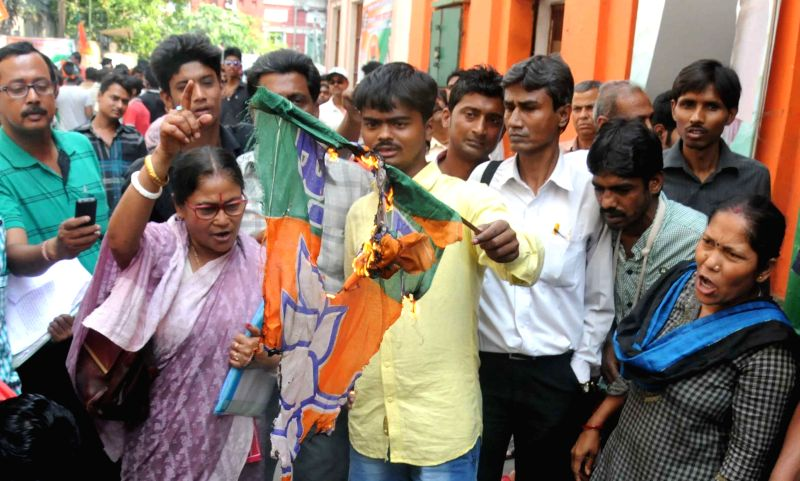 BJP workers burn party flags during a demonstration regarding tickets for upcoming Kolkata Municipal Corporation polls in front of party office in Kolkata, on March 24, 2015.