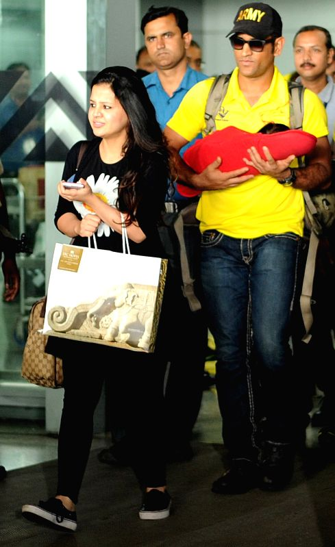Chennai Super Kings captain MS Dhoni arrives at Netaji Subhas Chandra Bose International Airport with his wife Sakshi and their daughter Ziva, in Kolkata on April 29, 2015. - MS Dhoni