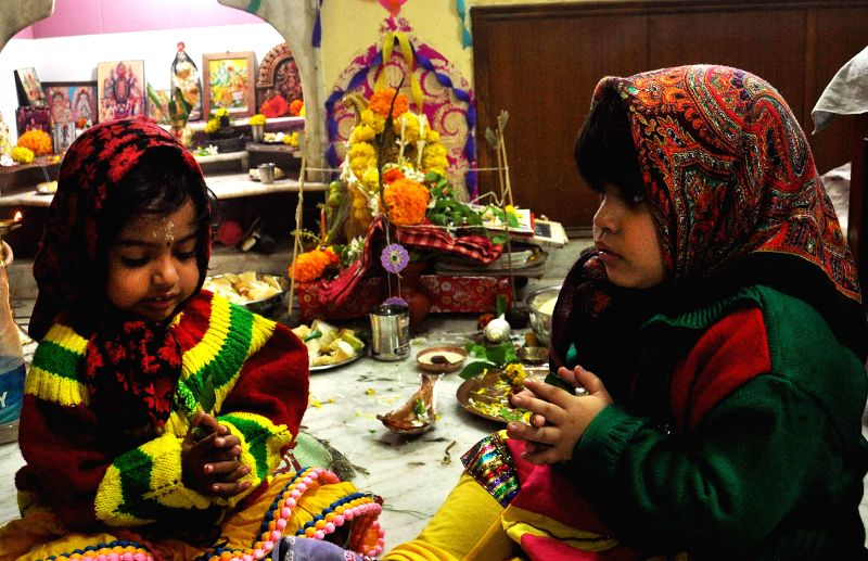 Children offer prayers to goddess Saraswati - the Hindu goddess of knowledge and arts, at their home in Kolkata, on Jan 25, 2015.