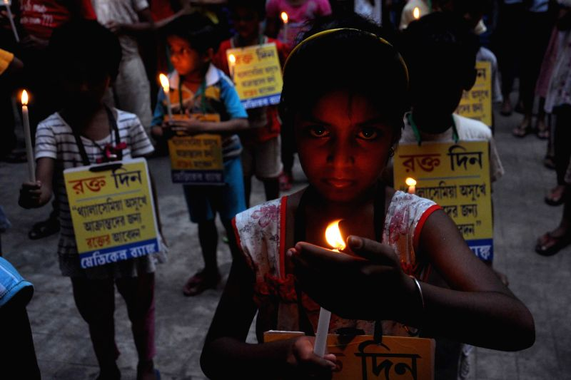 Children participate in a candlelight vigil on the eve of  International Thalassaemia Day in Kolkata, on May 7, 2015.