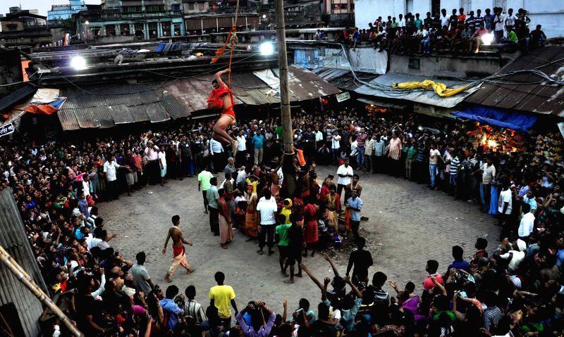 Devotees perform rituals during `Charak` celebrations in Kolkata on April 14, 2015.