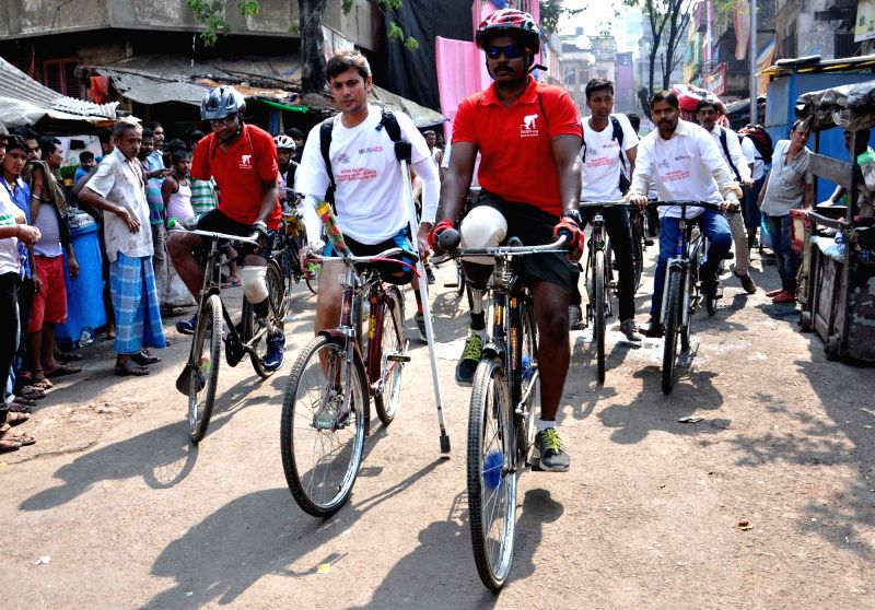 : Kolkata: Differently abled persons with other cyclist take part in a cycle rally against AIDS/HIV campaigning from Sonagachi, way to Petrapole border in Kolkata, on Nov 15, 2015. (Photo: Kuntal ...