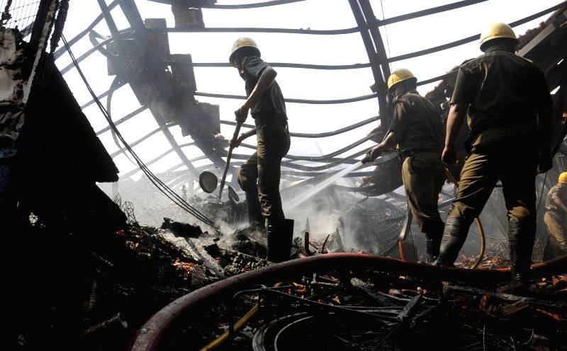Firefighter douse a fire that broke out at New Market, Kolkata on May 18, 2015.