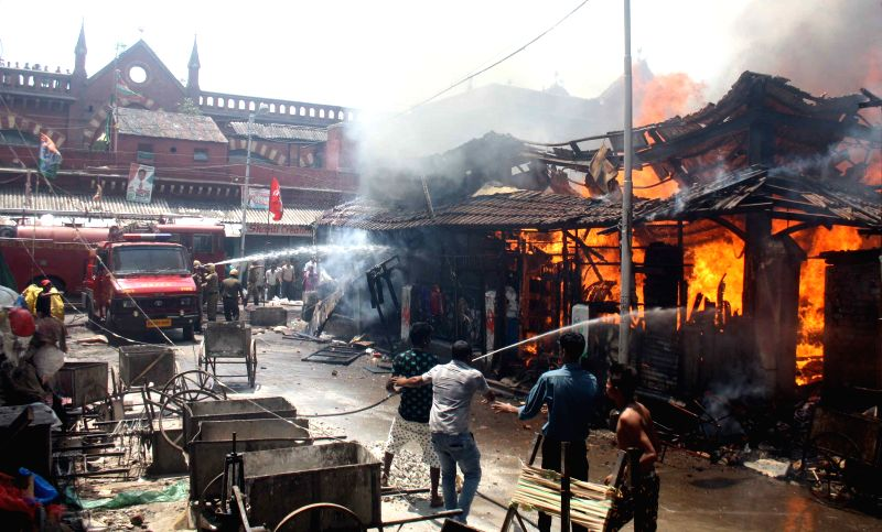 Firefighters douse a fire that broke out at New Market, Kolkata on May 18, 2015.