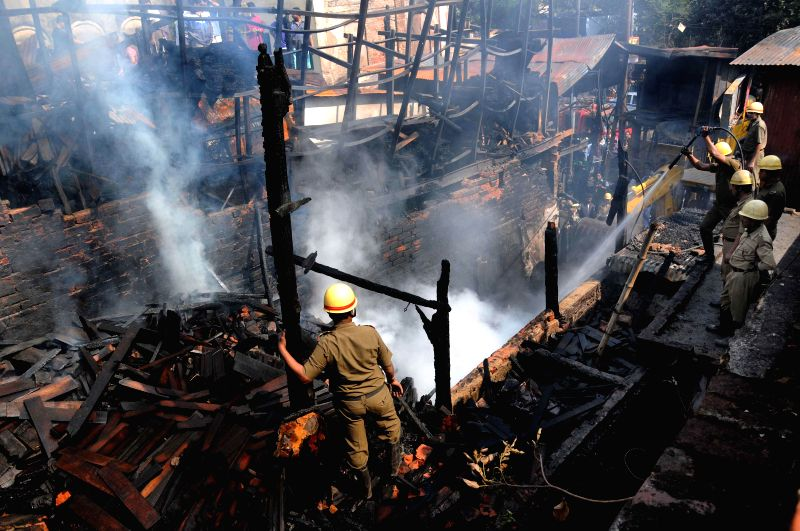 Firefighters still try hard to douse a fire that broke out at Bowbazar plywood godown on 2nd of Feb. in Kolkata on Feb. 3, 2015.