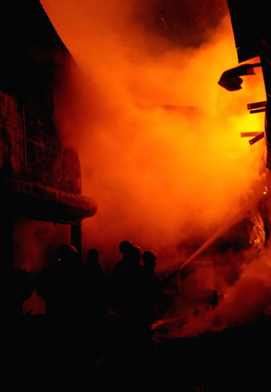 Firefighters try hard to douse a fire that broke out at Bowbazar plywood godown in Kolkata on Feb. 2, 2015.