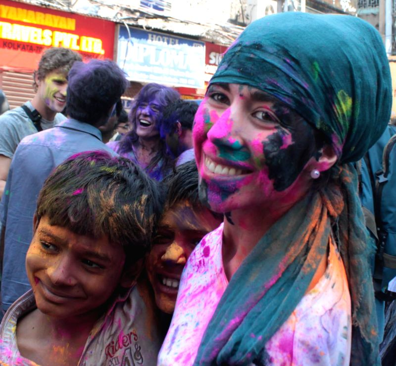 Foreign tourists play holi on the streets of Kolkata on March 5, 2015.