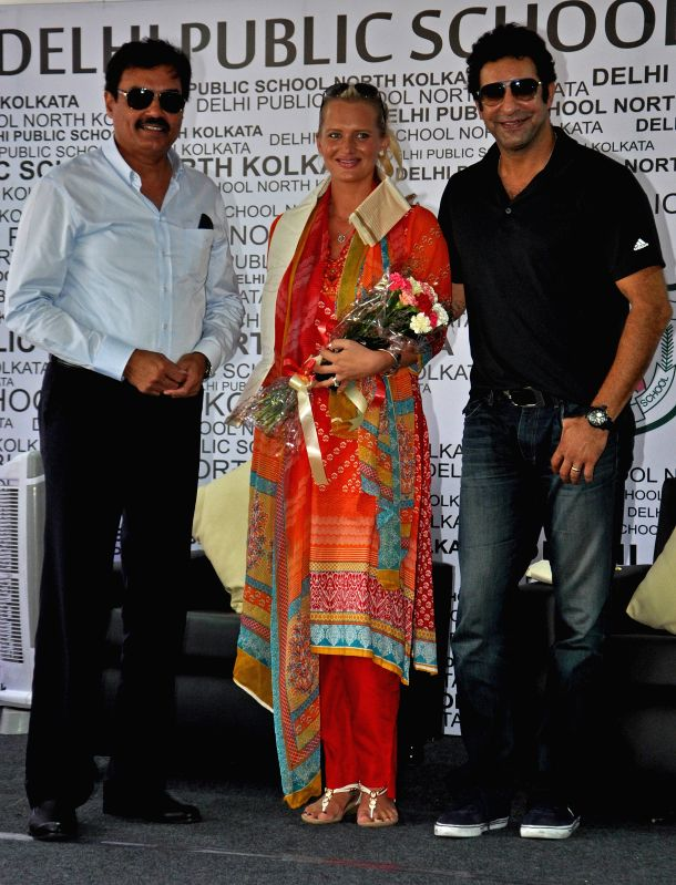 Formar Pakistani cricketer Wasim Akram with his wife and Indian cricketer Dilip Vengsarkar during a program at a school in Kolkata on May 5, 2015.