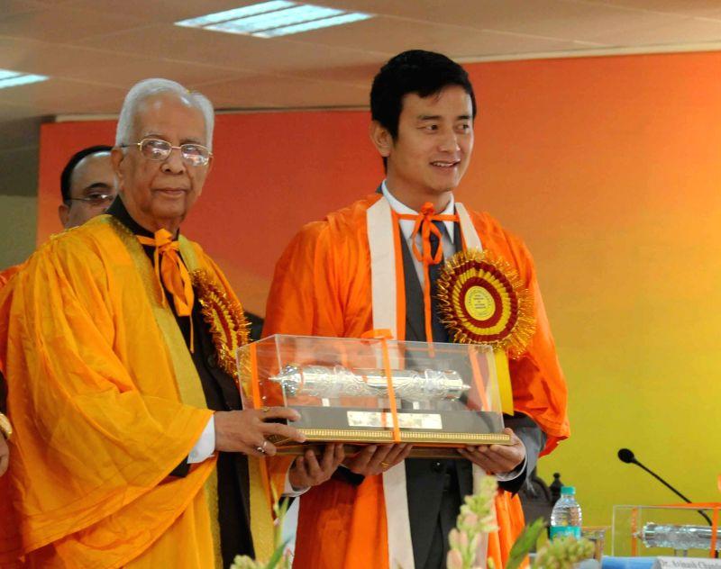 Governor K N Tripathi confers D.Lit (horn) to footballer Baichung Bhutia during the 59th Annual Convocation of Jadavpur University in Kolkata on Dec 24, 2014. - K N Tripathi
