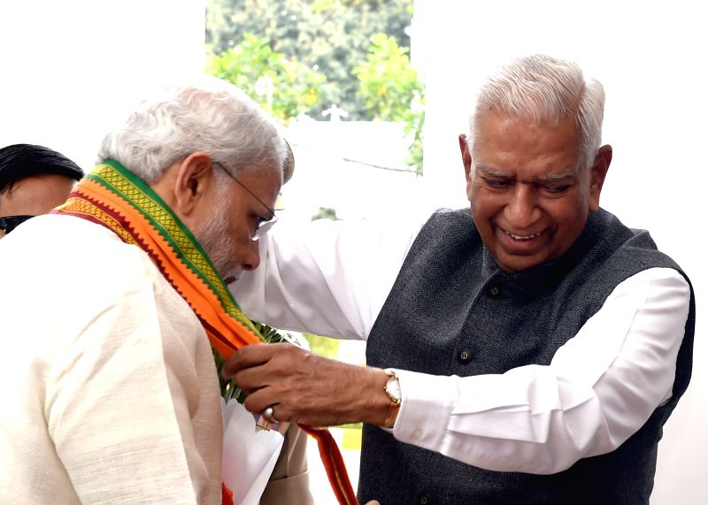 Karnataka Governor Vajubhai Rudabhai Vala  greets Prime Minister Narendra Modi on his arrival in Bengaluru on April 2, 2015. - Narendra Modi