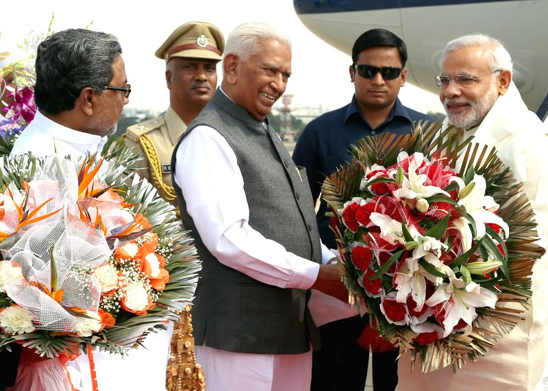 Karnataka Governor Vajubhai Rudabhai Vala and Chief Minister Siddaramaiah greet Prime Minister Narendra Modi on his arrival in Bengaluru on April 2, 2015. - Siddaramaiah and Narendra Modi
