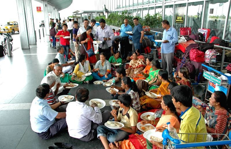 Passengers with their luggage waiting for transport outside at Netaji Subhas Chandra Bose International Airport during a 12 hour general strike called by opposition parties in Kolkata on ...
